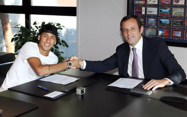 Neymar assina o contrato ao lado do ex-presidente do Barcelona, Sandro Rosell