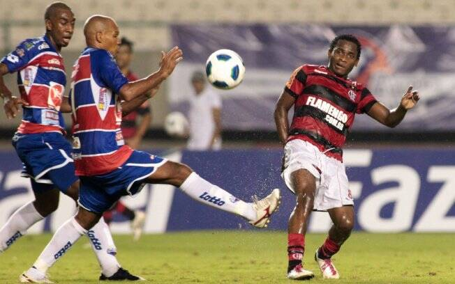 O flamenguista Willians tenta ganhar a disputa de bola com os rivais do Fortaleza